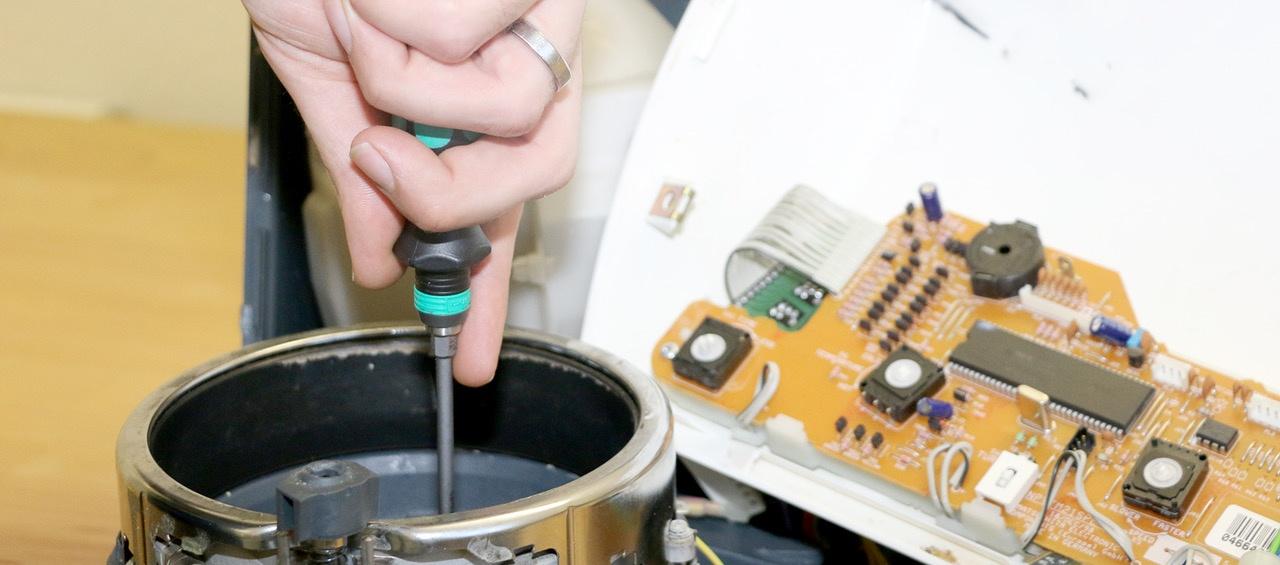 Hand mit Schraubenzieher die einen Thermomix TM21 repariert