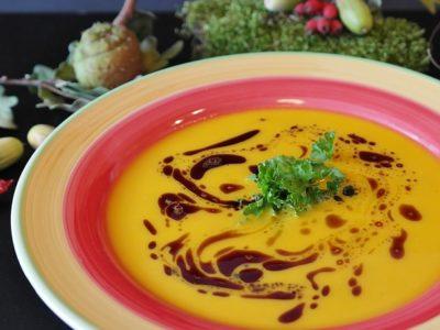 Teller mit Kürbissuppe, garniert mit Kürbisöl und Petersilie